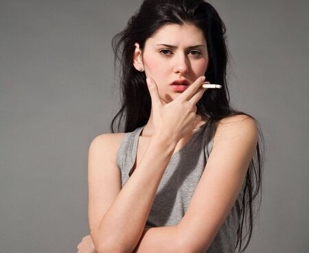 fashion style photo of a beautiful young brunette woman holding a cigarette,studio shot photo