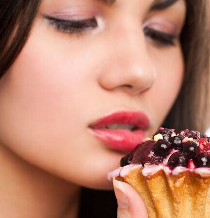Attractive black hair woman with a cake. Close-up studio portrait. photo