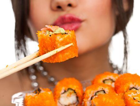 Schöne junge Frau, die Essen Sushi California roll. Flache Schärfentiefe, liegt Fokus auf die Sushi. isolierte, Studio.