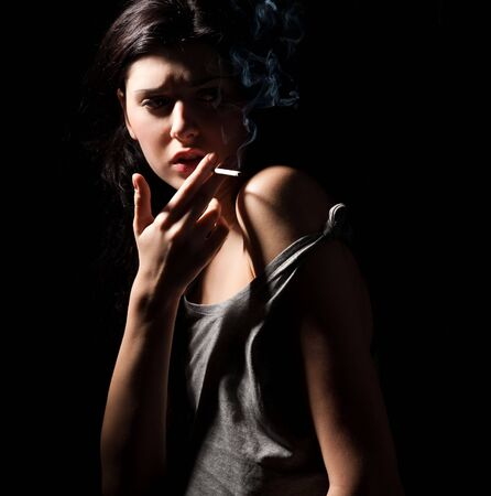 bad hair: portrait of smoking young woman with cigarette on black Stock Photo