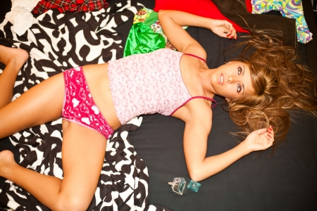 young teen blond woman is lying in bed in chaos of clothes photo