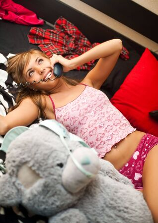 teen girl underwear: young teen blond woman in bed in chaos of clothes has telephone conversation