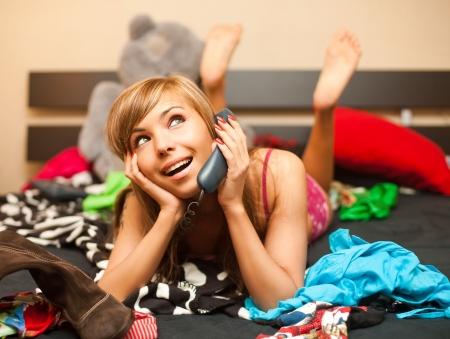 habitacion desordenada: joven rubia adolescente en cama en el caos de la ropa tiene conversaci�n telef�nica Foto de archivo