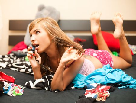 young teen blond woman in bed in chaos of clothes has telephone conversation photo