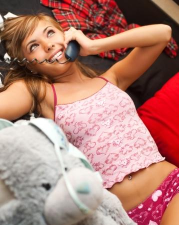 panties: joven rubia adolescente en cama en el caos de la ropa tiene conversaci�n telef�nica Foto de archivo