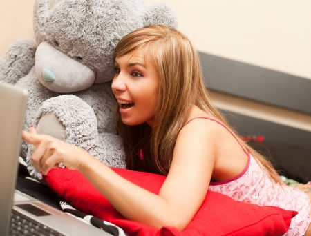 young teen blond woman in bed in chaos of clothes with laptop photo
