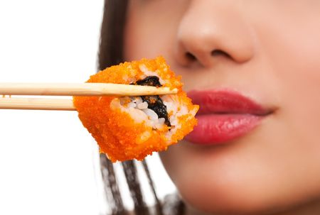 Beautiful young woman eating sushi california roll . Shallow depth of field, focus is on the sushi. isolated, studio. photo