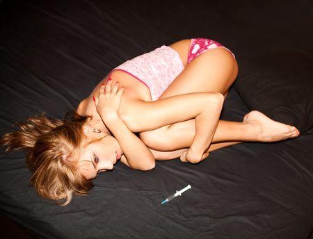 drogadiccion: joven narcomaniac, situada en la cama para dormir; la jeringa en hoja negra Foto de archivo