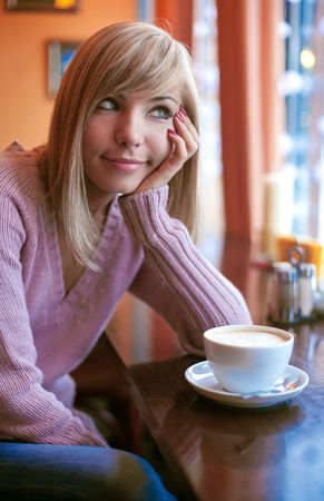 Young beautiful woman is sitting in cafe with a white cup and reading the newspaper Stock Photo - 6339423