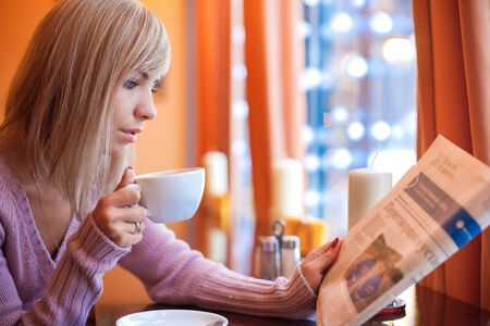 Young beautiful woman is sitting in cafe with a white cup and reading the newspaper photo