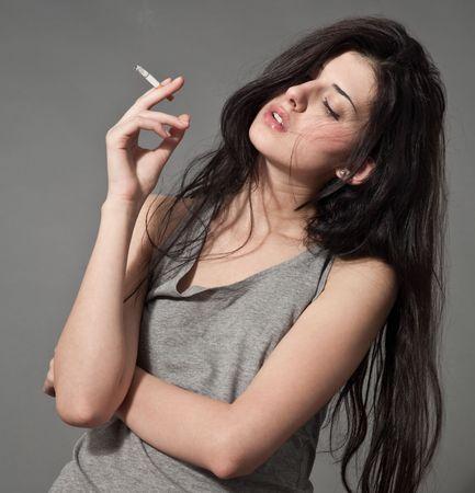 chica fumando: Close-up retrato de mujer de fumar de joven de pelo negro con cigarrillo Foto de archivo