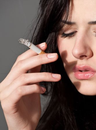cigarette smoke: close-up portrait of young black hair smoking woman with cigarette Stock Photo