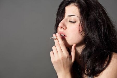 smoking girl: close-up portrait of young black hair smoking woman with cigarette Stock Photo