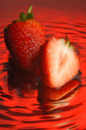 Strawberry and water on a mirror