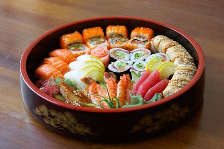 Sushi and rolls on the tray on the table. Stock Photo
