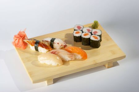 Sushi and rolls on the tray on the light background.