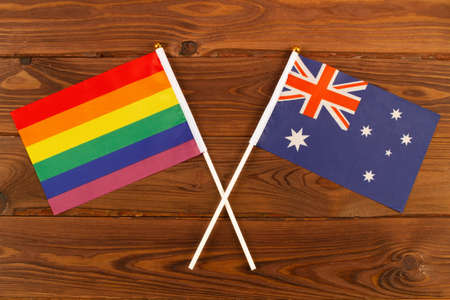 Rainbow flag and flag of Australia on brown wood planks background. Pride Month. Close Up. Top view Foto de archivo