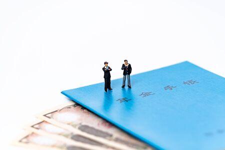 Miniature Businessman on Pension Book