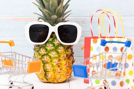 A pineapple  wearing sunglasses and shopping carts Banco de Imagens