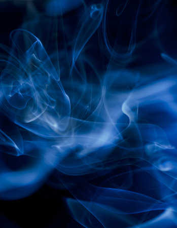 Thick, scenic clouds of smoke. From incense, or cigarettes, or cigars. Indoors. In the rays of sunshine on a dark background. Psychedelic mood. Close up. Colorful abstract background.