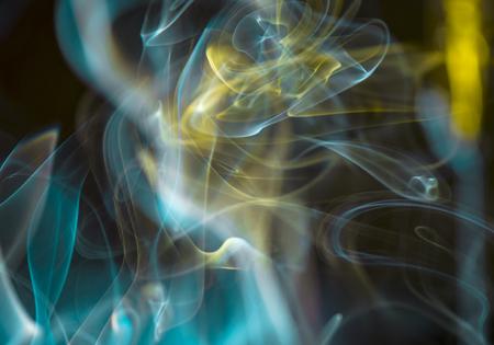 煙の厚い、風光明媚な雲。お香、タバコ、または葉巻。屋内で。暗い背景に太陽の光線。サイケデリックなムード。クローズ アップ。カラフルな抽 写真素材