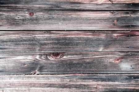 Fragment of the wall of the old wooden house in the Belorussian village. Beautiful vintage background of wooden boards with colorful texture. Copy space to add your text.