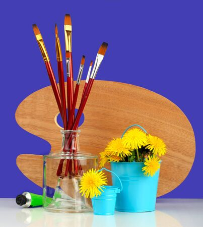 brushes with the palette and dandelions photo