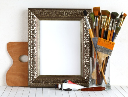 Picture gold frame with a palette and paintbrushes  photo