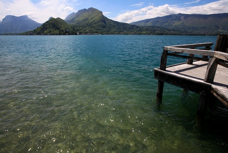 Wide angle view of a pontoon on a lake with mountains in the horizon, lake Annecy, France.