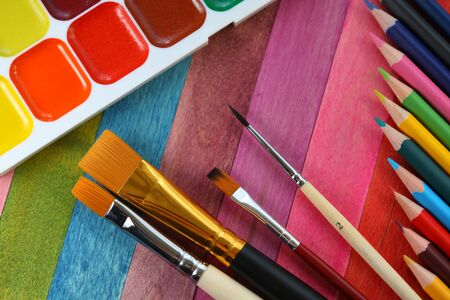 watercolor paints with brushes and colorful pencils Stock Photo