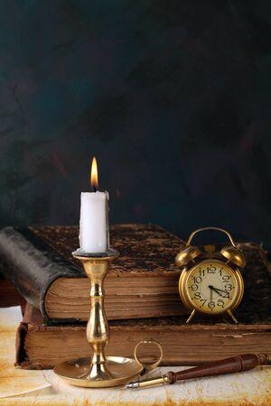 libros antiguos: Vela con libros y un reloj despertador Foto de archivo