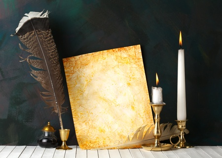 scribe: Old paper with a candles and a quill pen