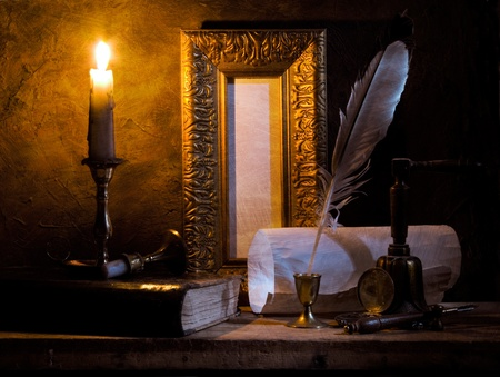 STILL-LIFE.Old paper with a candle and a quill pen