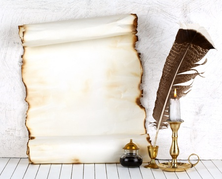 Old paper with a candle and a quill pen.On a white background. Stock Photo - 10872266