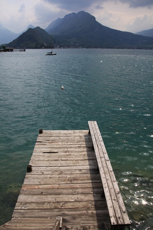 Wide angle view of a pontoon on a lake with mountains in the horizon, lake Annecy, France. photo