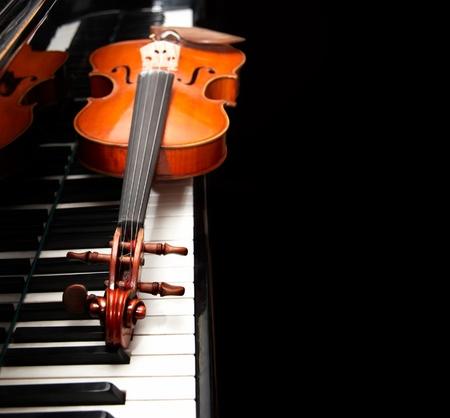 Viool op de piano op een zwarte achtergrond  Stockfoto