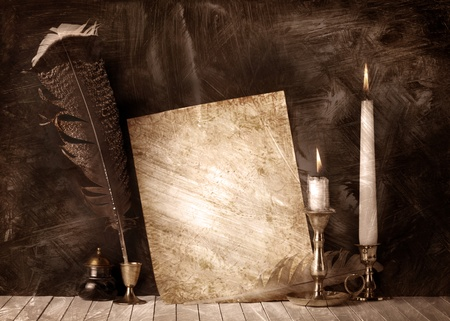 Old paper with a candles and a quill pen photo