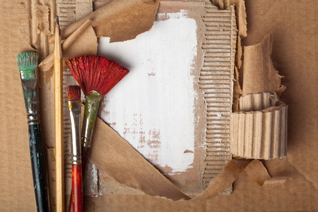 Brushes and pencil on cardboard background Stock Photo