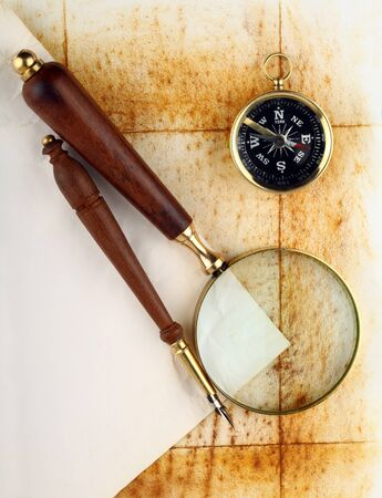 Compass and magnifier  on old textured paper