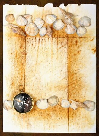 Compass on old textured paper with sea cockleshells photo