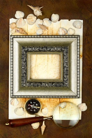 antique frame with a compass, cockleshells and a magnifier photo
