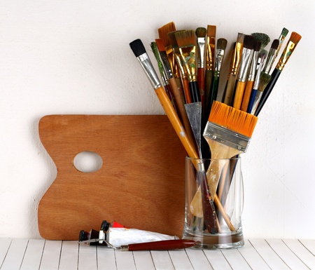 Palette with paintbrush and a paint