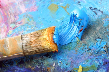 Bright colored paint with a brush on a palette. photo