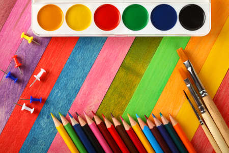 art and craft equipment: watercolor paints with brushes and colorful pencils