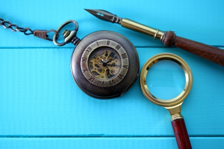 antique pocket watch with a magnifying glass and an old pen photo