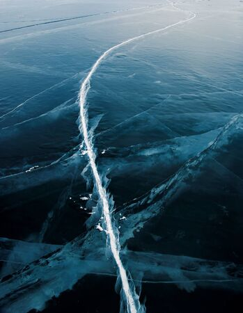 Beautiful ice of Lake Baikal with abstract cracks photo