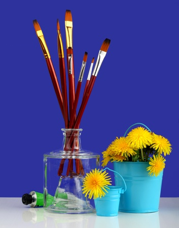 paint brushes and paint with dandelions