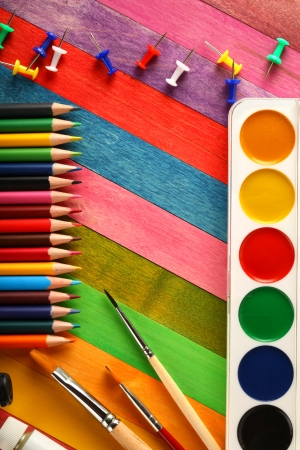 Watercolor paints with brushes and colorful pencils