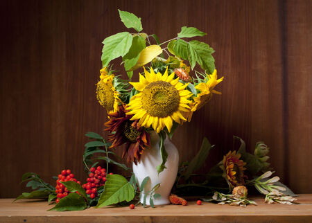 still life with sunflowers and mountain ash on a wooden background photo