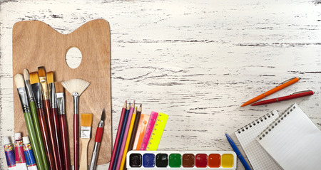 large group of items: palette with brushes and paints on a wooden table Stock Photo